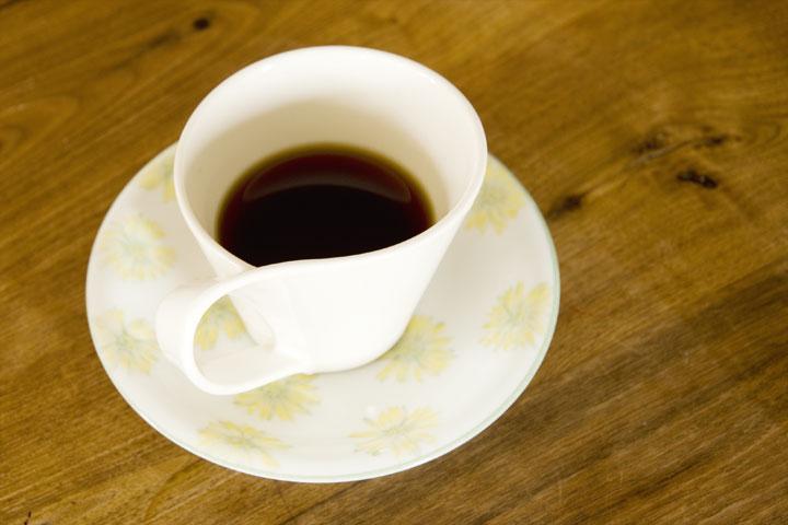 木肌のテーブルにホワイト基調のコーヒーカップで、癒やしのひととき。